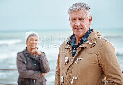 Buy stock photo Cropped portrait of a handsome senior man and his wife standing outside at the beach
