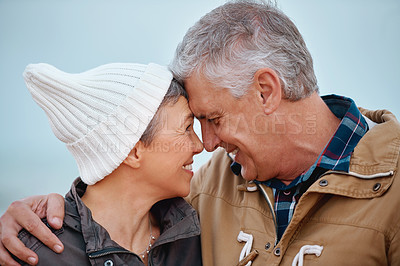 Buy stock photo Cropped shot of an affectionate senior couple standing outside at the beach