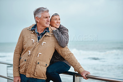 Buy stock photo Cropped shot of an affectionate senior couple standing on the promenade at the beach