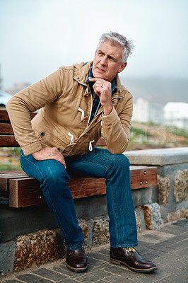 Buy stock photo Full length shot of a handsome senior man looking thoughtful while sitting on a bench near the beach