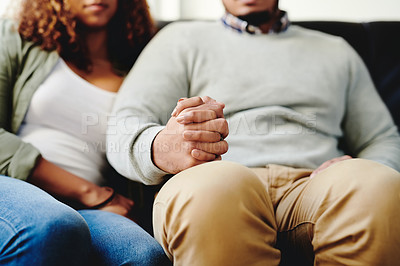 Buy stock photo Cropped shot of an unrecognizable couple holding hands on the couch in the living room at home