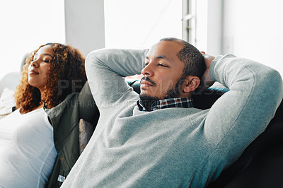 Buy stock photo Cropped shot of a young couple chilling with their hands behind their heads on the couch in the living room at home
