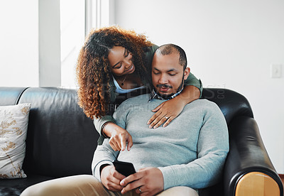 Buy stock photo Cropped shot of a young couple using a cellphone together on the couch in the living room at home