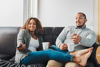 Buy stock photo Cropped shot of a young couple watching tv while chilling on the couch in the living room at home