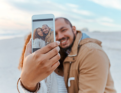Buy stock photo Shot of a loving young couple taking a selfie on the beach