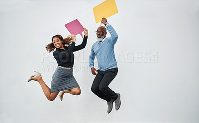 Buy stock photo Studio shot of a mature businessman and young businesswoman holding speech bubbles and jumping