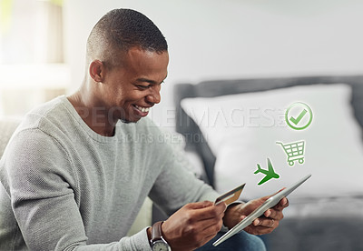 Buy stock photo Cropped shot of a handsome young man doing online bookings in the living room at home