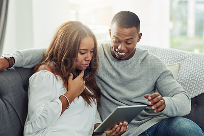 Buy stock photo Cropped shot of a young attractive couple using a tablet together on the sofa in the living room at home
