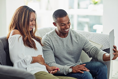 Buy stock photo Cropped shot of a young attractive couple taking a selfie using a tablet on the sofa at home