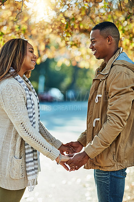 Buy stock photo Cropped shot of a young attractive couple in a public park outside