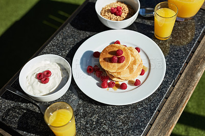 Buy stock photo Shot of pancakes and juice on a table outdoors