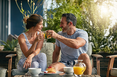 Buy stock photo Shot of a mature couple enjoying breakfast together outdoors
