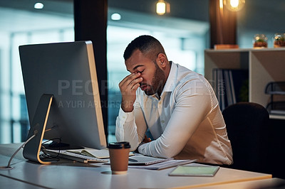 Buy stock photo Shot of a young businessman experiencing stress during late night at work