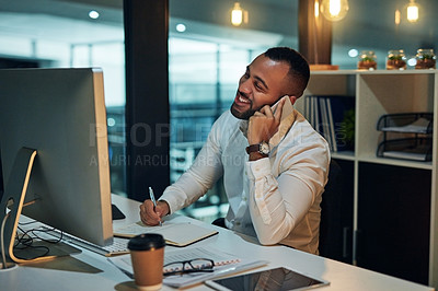 Buy stock photo Shot of a young businessman using a computer and mobile phone during a late night in a modern office
