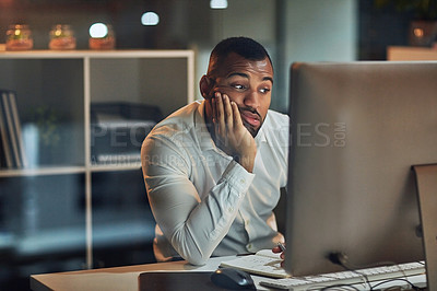 Buy stock photo Shot of a young businessman looking bored while working at his desk during late night at work