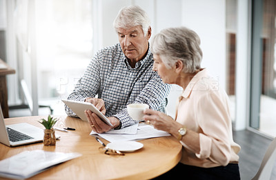 Buy stock photo High angle shot of a senior couple working on their finances at home