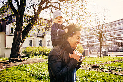 Buy stock photo Cropped shot of a handsome father piggybacking his baby boy through the park