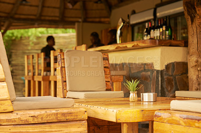 Buy stock photo Shot of the bar area with tables and chairs inside of a holiday resort during the day