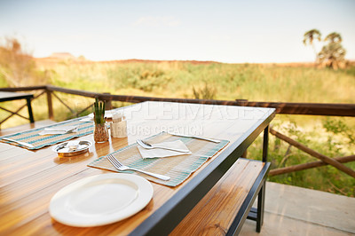 Buy stock photo Shot of a simple set table with a breathtaking view inside of a holiday resort during the day