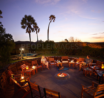 Buy stock photo High angle shot of a fire pit surrounded with chairs and guests inside of a holiday resort during the evening