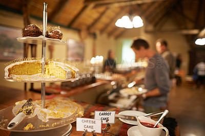 Buy stock photo Closeup of a tray of desserts on a table with guests in the background dishing up food for dinner inside of a holiday resort