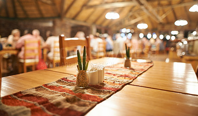 Buy stock photo Shot of a simple set unoccupied table with guests in the background having dinner inside of a holiday resort during the night