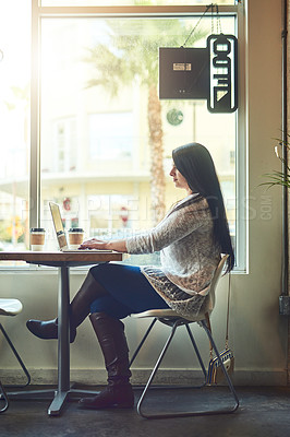 Buy stock photo Shot of a young woman using a laptop in a cafe