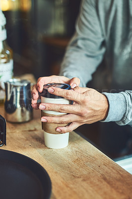 Buy stock photo Closeup shot of an unrecognizable barista closing a cup of freshly brewed coffee in a cafe