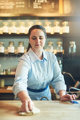 Buy stock photo Shot of a young woman cleaning a countertop in her cafe