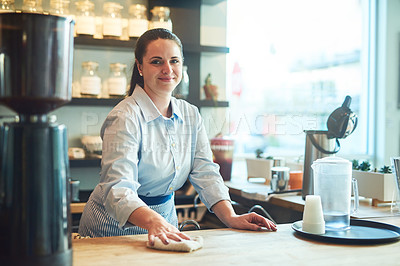 Buy stock photo Portrait of a young woman cleaning a countertop in her cafe