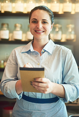 Buy stock photo Portrait of a young waitress holding a notebook in a cafe