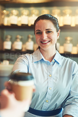 Buy stock photo Portrait of a young barista giving a cup of coffee to a customer in a cafe