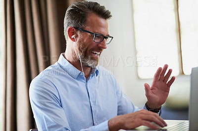 Buy stock photo Shot of a mature businessman waving while using a laptop to work from home