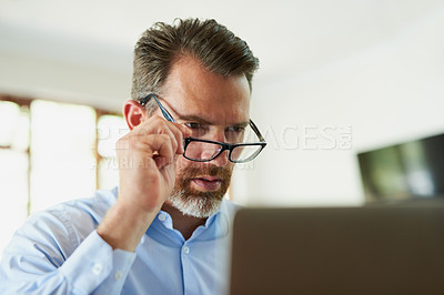 Buy stock photo Shot of a mature businessman using a laptop to work from home