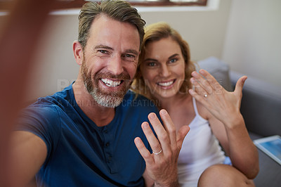 Buy stock photo Shot of a happy middle aged couple taking a selfie and showing off their wedding rings at home