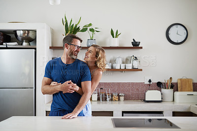 Buy stock photo Shot of a happy middle aged couple embracing in the kitchen at home