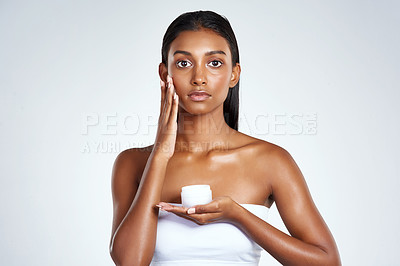 Buy stock photo Studio shot of a beautiful young woman applying moisturizer to her face against a light background