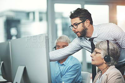 Buy stock photo Shot of a young man helping his senior colleagues in a call center
