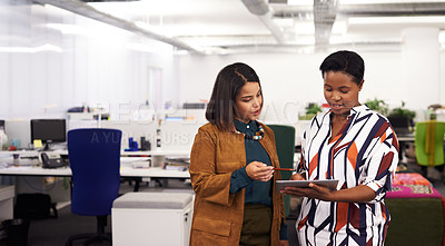 Buy stock photo Shot of two young businesswomen using a digital tablet together while having a discussion in a modern office
