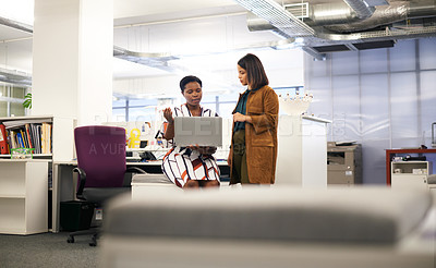Buy stock photo Shot of two young businesswomen using a laptop together while having a discussion in a modern office
