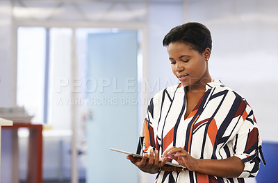 Buy stock photo Shot of a confident young businesswoman using a digital tablet in a modern office