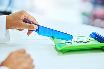 Buy stock photo Cropped shot of an unrecognizable female pharmacist separating medication in the pharmacy
