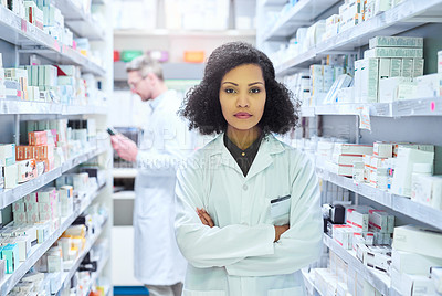 Buy stock photo Portrait of a confident young woman working in a pharmacy with her colleague in the background
