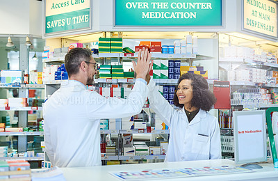 Buy stock photo Shot of a mature man and young woman giving each other a high five while working in a pharmacy
