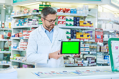 Buy stock photo Shot of a pharmacist holding up a tablet with a chromakey screen
