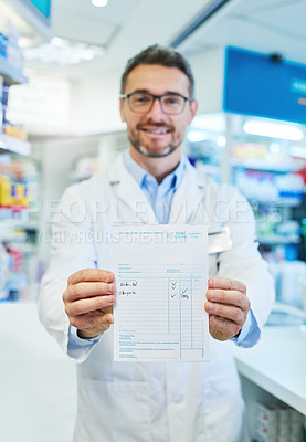 Buy stock photo Shot of a pharmacist holding up a prescription