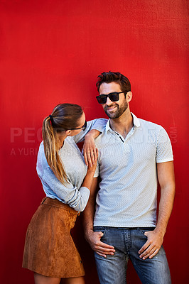 Buy stock photo Shot of a fashionable young couple leaning against a red wall outside