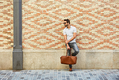 Buy stock photo Shot of a fashionable young man leaning against a brick wall outside