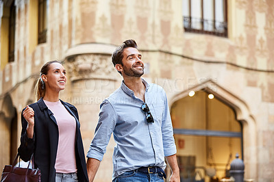 Buy stock photo Shot of an affectionate young couple walking hand in hand together in the city