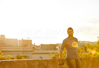 Buy stock photo Cropped shot of a man on a rooftop against a city background